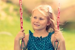 Little girl is riding on a swing Royalty Free Stock Photos