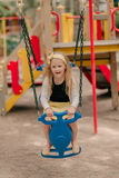 Little girl is riding on a swing Stock Image