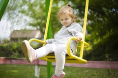 Little girl riding on a swing and waving her legs stock image