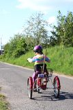 Little girl riding a three wheel bike Royalty Free Stock Photos