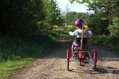 Little girl riding a three wheel bike Stock Photography