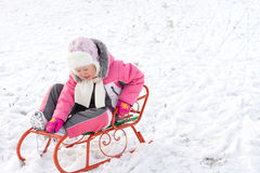 Little girl riding a toboggan in snow Royalty Free Stock Images