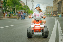 Little girl riding toy car Stock Photos