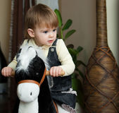 Little girl riding a toy horse Royalty Free Stock Photo