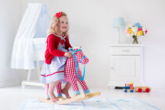 Little girl riding a toy horse Royalty Free Stock Images