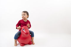 Little girl riding a toy horse Stock Images