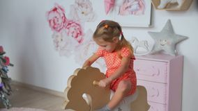 Little girl riding a toy rocking horse. Little girl riding toy rocking horse in the room in pink colors stock video