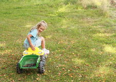 Little girl riding a tractor Royalty Free Stock Images