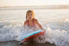 Little girl riding wave on boogie board. In ocean stock photo