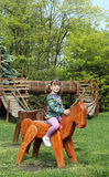 Little girl riding wooden horse Royalty Free Stock Image