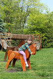 Little girl riding wooden horse on playground Royalty Free Stock Image