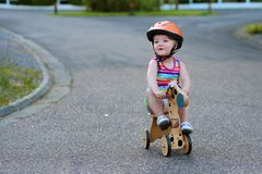 Little girl riding wooden tricycle on the street Royalty Free Stock Images