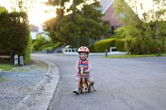 Little girl riding wooden tricycle on the street Stock Images