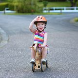 Little girl riding wooden tricycle on the street. Happy little kid, cute blonde toddler girl in colorful dress and orange safety helmet playing outdoors on the Royalty Free Stock Photos