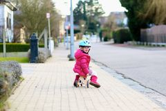 Little girl riding wooden tricycle on the street. Happy little kid, cute blonde toddler girl in pink jacket and blue safety helmet playing outdoors on the street Royalty Free Stock Images