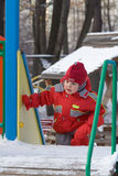 Little girl rises on an ice slope. The little girl in the red rises on an ice slope Stock Images