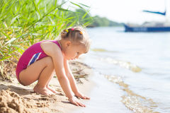 Little girl on the river bank touching the wave Royalty Free Stock Images