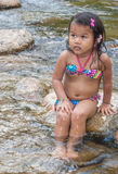 Little girl on the river. Little girl sitting in the cold river stock images