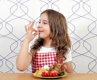 Little girl with roasted chicken wings and ok hand sign Royalty Free Stock Photos