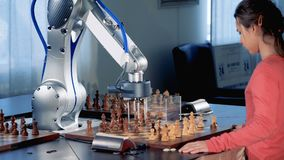 Little girl and robotic arm are capturing chess pieces of each other while playing