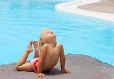 Little girl on a rock near pool Royalty Free Stock Photography