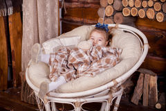 Little girl in rocking chair near fireplace Royalty Free Stock Image