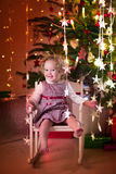 Little girl in rocking chair under Christmas tree Stock Photo