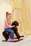 Little girl rocks on hobbyhorse Royalty Free Stock Photography
