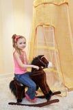 Little girl rocks on rocking horse Stock Image