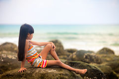Little girl on a rocky seashore Stock Photography