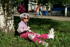 Little girl in roller blades sitting on the grass. Under tree Royalty Free Stock Photo