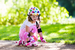Little girl with roller skate shoes in a park. Little girl learning to roller skate in sunny summer park. Child wearing protection elbow and knee pads, wrist Stock Photo
