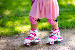Little girl with roller skate shoes in a park. Little girl learning to roller skate in sunny summer park. Child wearing protection elbow and knee pads, wrist Stock Photography