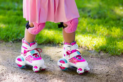 Little girl with roller skate shoes in a park. Little girl learning to roller skate in sunny summer park. Child wearing protection elbow and knee pads, wrist Royalty Free Stock Image