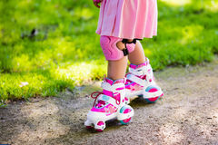 Little girl with roller skate shoes in a park. Little girl learning to roller skate in sunny summer park. Child wearing protection elbow and knee pads, wrist Royalty Free Stock Photos