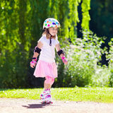 Little girl with roller skate shoes in a park Stock Images