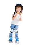 Little girl in roller skates with bon-bon Royalty Free Stock Image