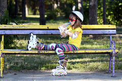 Little girl with roller skates drink water Stock Photography