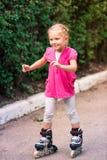 Little girl on roller skates at park Stock Photos