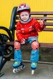 Little girl in roller skates sitting on bench Stock Image