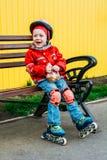Little girl in roller skates sitting on bench Stock Images