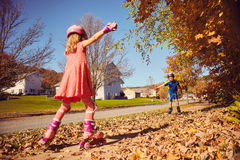 Little girl roller skating to her male friend stock image