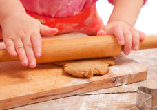 Little girl rolling a gingerbread dough Stock Images