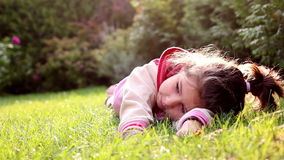 A little girl is rolling in the grass stock video footage