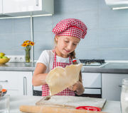 Little girl rolling out a dough Royalty Free Stock Image