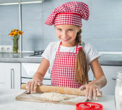 Little girl rolling out a dough Stock Images