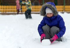 Little girl rolling snowball in winter. Stock Photo