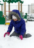 Little girl rolling snowball. Royalty Free Stock Photo