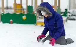 Little girl rolling snowball. Stock Photo