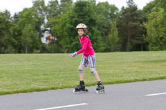 Little girl rolller skating in a park Royalty Free Stock Photos
